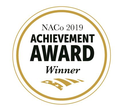 Gold Circle  with Black Text denoting NACo 2019 Achievement Award Winner