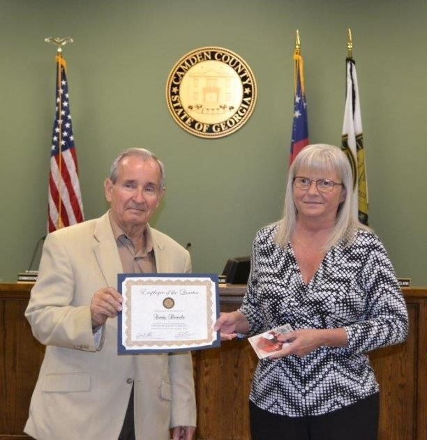 Commission Chair Jimmy Starline handing certificate to Employee of the Quarter Cindy Daniels